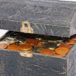 Stock Photo: Many coins in one old chest isolated