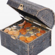 Many coins in one old chest isolated — Stockfoto