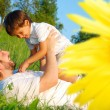 Happy childhool on green meadow, behind sunflower — Stock Photo #8848568