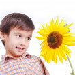 Very cute boy standing behind sunflower as friend — Stock Photo #8848598