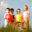 Happy small group of children on meadow — Stok fotoğraf
