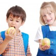 Two happy school children eating an apple — Stock Photo