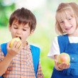 Two very cute children eating fruits outdoor — Stock Photo