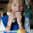 Little cute girl in classroom,  eating - Foto Stock