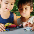Stock Photo: Children playing with cars toys outdoor in summer time
