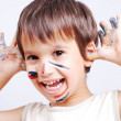 Little cute kid with colors on his face - Stock Photo