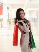 Hermosa mujer compra en un centro comercial sonriendo — Foto de Stock