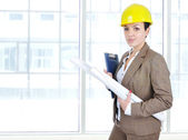 Architect woman in business suit portrait with yellow helmet and blueprints — Stock Photo