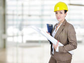 Female architect holding blueprints with helmet on head — Stock Photo