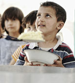 Refugee camp, poverty, hungry children receiving humanitarian food — Stock Photo