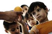 Pobreza campamento, refugiados, niños hambrientos recibiendo alimentos humanitaria — Foto de Stock