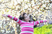 Pretty little girl in the establishment of branches of a blossoming apple — Stock Photo