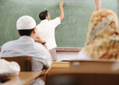 Muslim arabic teacher writing on board — Stock Photo