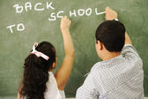 Back to school - boy and girl writing on board in classroom — Stock Photo