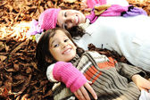 Cute boy lying in the Autumn fall leaves with his mother — Stock Photo
