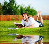 Mutlu genç bir adam çayır okuma — Stok fotoğraf