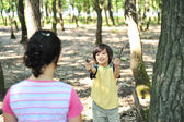 Children playing in wonderfull forest and collecting small pieces of wood — Stock Photo