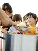 Hungry children in refugee camp, distribution of humanitarian food — Foto Stock