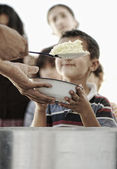 Hungry children in refugee camp, distribution of humanitarian food — Stok fotoğraf
