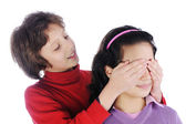 Girl covering a girls eyes to see if she can guess who is behind her — Foto Stock