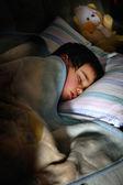Oyuncak ayı ile karanlık odada uyuyan çocuk — Stok fotoğraf