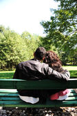 Young loving couple on the bench in park — Foto Stock