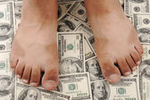 Dollars background, human feet, standing on — Stock Photo