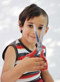 Kid cutting hair to himself with scissors, funny look — Stock Photo