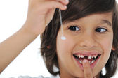 Lost milk-tooth, cute boy with long hair holding his tooth on thread — Fotografia Stock