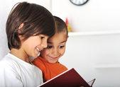 Mutlu sevimli çocuklar evde, sevimli küçük kardeşler okuma — Stok fotoğraf