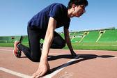 Jeune athlète masculin est au début du tapis roulant au stade — Photo