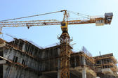Buildings under construction and cranes under a blue sky — Stock Photo