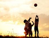 Silueta, skupina šťastných dětí hraje na louce, západ slunce, léto — Stock fotografie