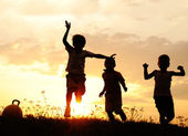 Silhouette, group of happy children playing on meadow, sunset, summertime — Zdjęcie stockowe