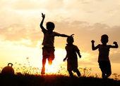 Siluet, grup mutlu çocuklar oynarken çayır, günbatımı, yaz — Stok fotoğraf
