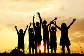 Silueta, grupo de niños felices jugando en el prado, puesta de sol, verano — Foto de Stock