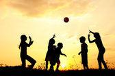 Sylwetka, grupa szczęśliwy dzieci bawiące się na łące, zachód słońca, lato — Zdjęcie stockowe