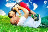 A parent and little boy laying on grass — Stock Photo