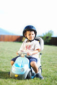 Child on green meadow driving a playing car — Stock Photo