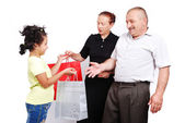 Cute girl is giving a present to her (grand)parents — Stok fotoğraf