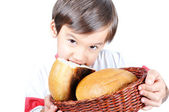 A little cute kid holding bread and biting it — Stok fotoğraf
