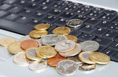 Many coins in one place on laptop keyboard — Stock Photo