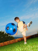 Little cute kid is hitting ball by his foot — Stok fotoğraf