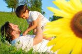 Ayçiçeği arkasındaki yeşil çayır üzerinde mutlu childhool — Stok fotoğraf