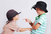 Two mates with hats pointing by finger on each other — Stock Photo