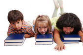Three children laying down on books, isolated — Stock Photo