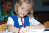 Petite fille mignonne dans la salle de classe, écriture — Photo