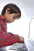 Cute kid sitting with laptop — Stock Photo