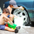 Stock Photo: A little cute kid is cleaning car, outdoor