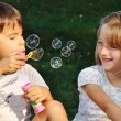 Happy cute children playing with bubbles — Stock Photo